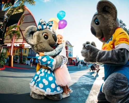 dreamworld-little-girl-in-pink-tutu-with-balloons-hugging-belinda-koala-with-kenny-koala