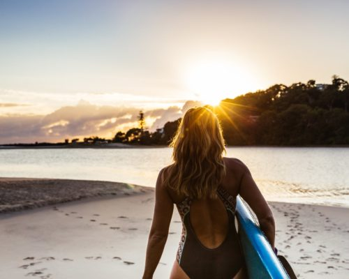 girl-walking-along-beach-with-paddleboard-at-sunrise-at-currumbin-creek