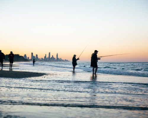 men-with-fishing-poles-on-the-beach-at-currumbin-burleigh-with-surfers-paradise-skyline